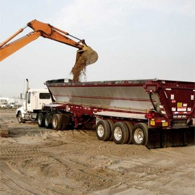A contruuction trailer with a backhoe dumping dirt into it