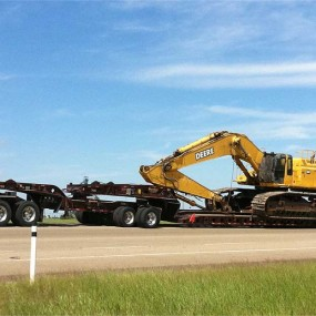 Heavy Haul trailer carrying yellow backhoe
